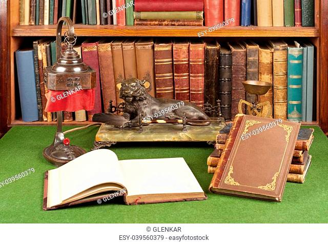 Antique leather books, lamp and reading glasses on green blotter