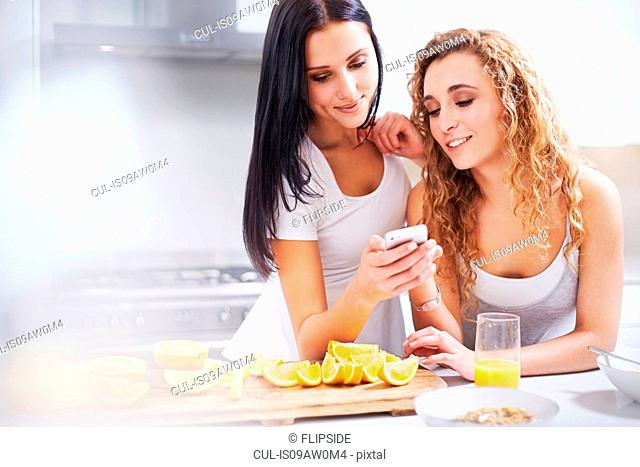Two young women reading smartphone text at kitchen counter