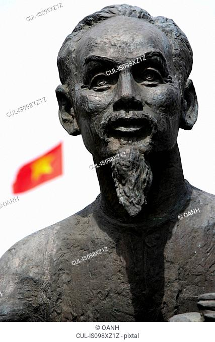 Statue of Ho Chi Minh with Vietnamese flag in background