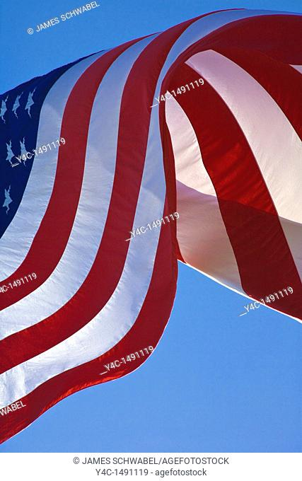 United States American flag known as Stars and Stripes blowing in the wind aganist a blue sky