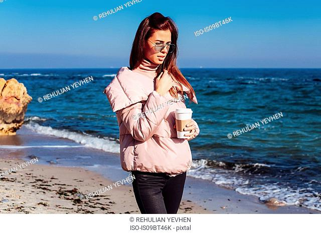 Stylish mid adult woman strolling on beach with takeaway coffee, Odessa, Odeska Oblast, Ukraine