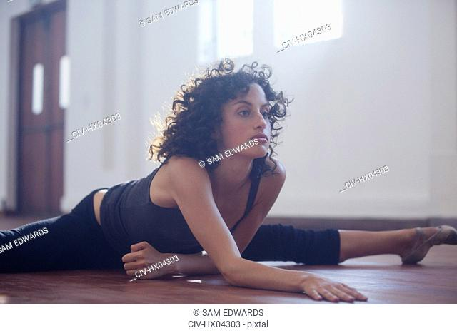Strong young female dancer stretching in dance studio