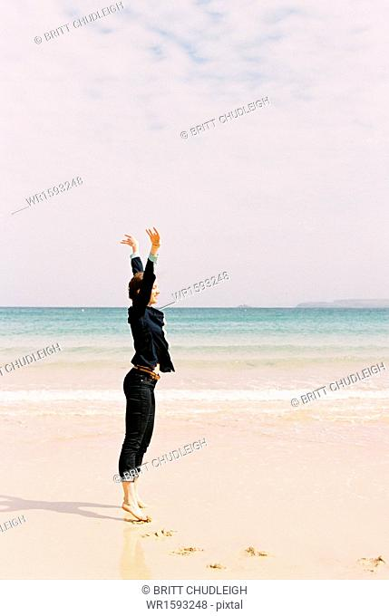 A woman standing barefoot on the sand raising her arms above her head, in a gesture