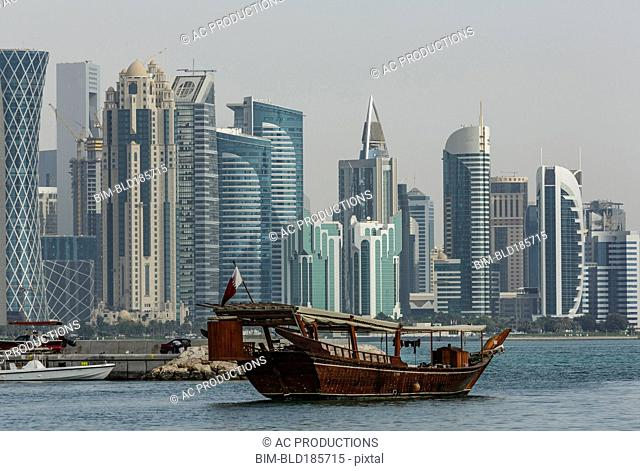 Boat floating near Doha skyline, Doha, Qatar