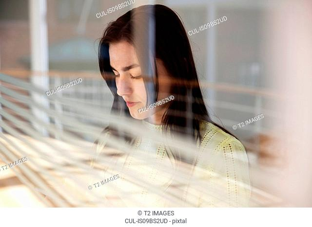 Teenage girl reading text message on cellphone by glass wall