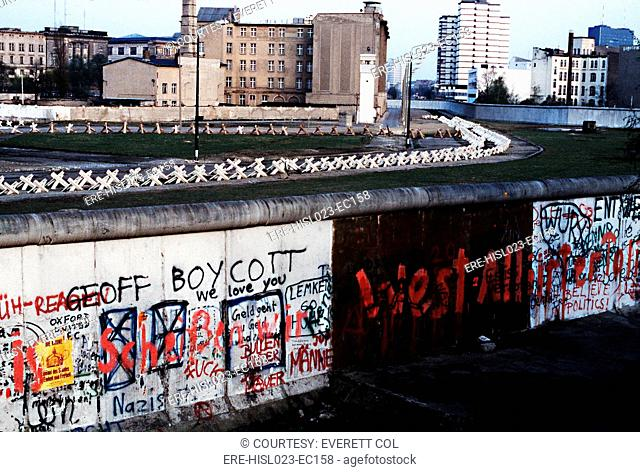 The Berlin Wall separated Communist-controlled East Germany from West Berlin. White apartments of West Berlin contrast with the boarded up vacant brick...