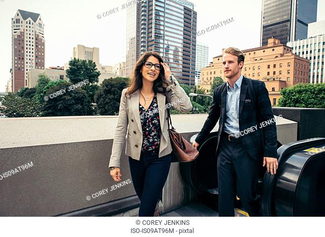 Businessman and woman stepping off escalator, Los Angeles, USA