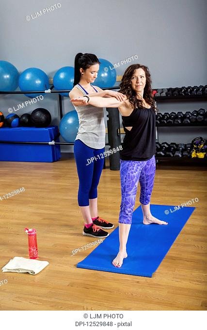 An attractive middle-aged woman doing yoga exercises at the gym with her personal trainer providing assistance; Spruce Grove, Alberta, Canada