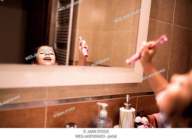 Mirror image of little girl standing in the bathroom going to brush her teeth