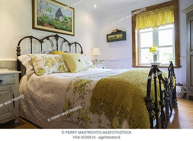 King size bed with white and yellow flowery bedspread and antique wrought iron headboard and footboard in master bedroom inside an old 1892 Canadiana cottage...