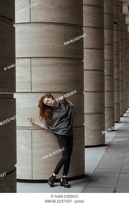 Carefree Caucasian woman leaning on pillar