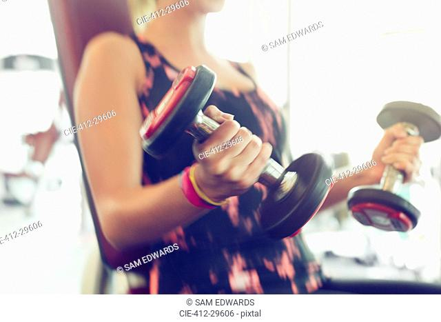 Blurred motion doing dumbbell biceps curls at gym