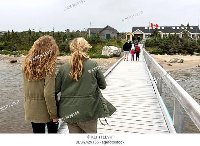 Tourists walking on dock towards buildings on shore, Gros Morne National Park; Newfoundland, Canada