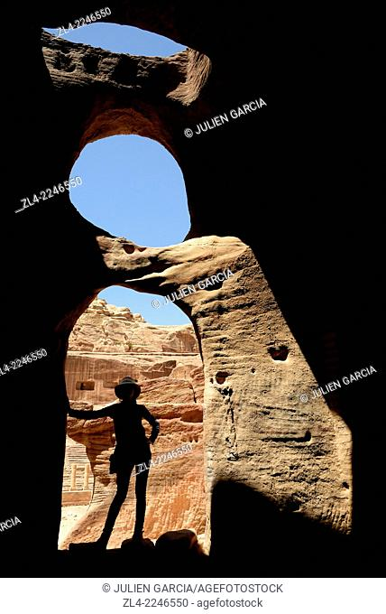 Silhouette of a woman at the entrance of a cave near the theatre. Jordan (Hashemite Kingdom of), Ma'an Governorate (Maan), ancient city of Petra