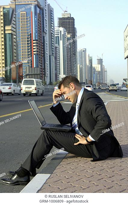 Businessman sitting on Shaikh Zayed Road in Dubai and working on laptop