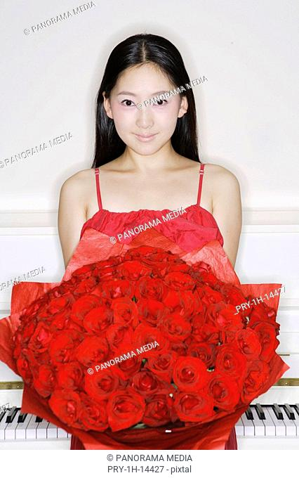 Portrait of a young woman holding bouquet of red roses