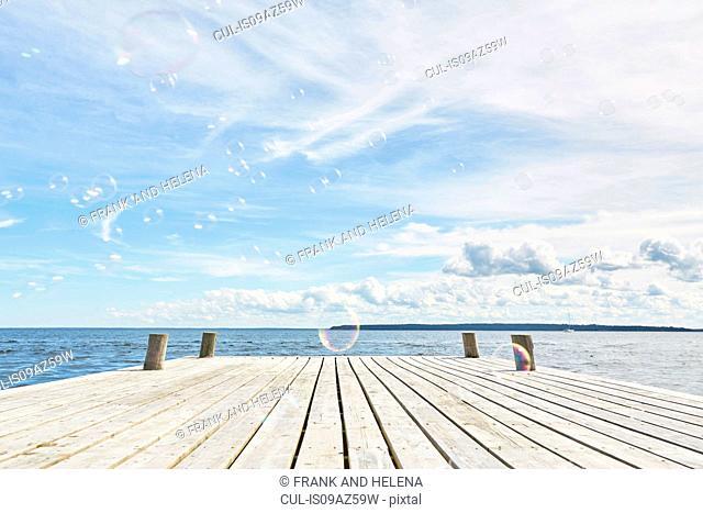 Bubbles floating across empty wooden pier