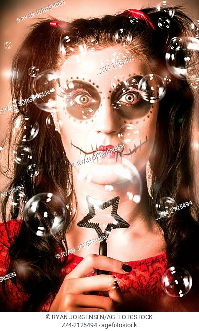 Creative portrait of a day of the dead girl with sugar skull makeup blowing party bubbles through a black star blower with a serious look of shock