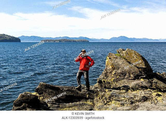Man talks on a cell phone on a cliff above Tongass Narrows near Ketchikan, Southeast Alaska, Spring