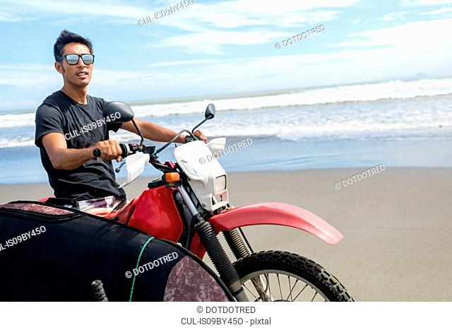 Motorcyclist carrying surfboard on sandy beach, Abulug, Cagayan, Philippines
