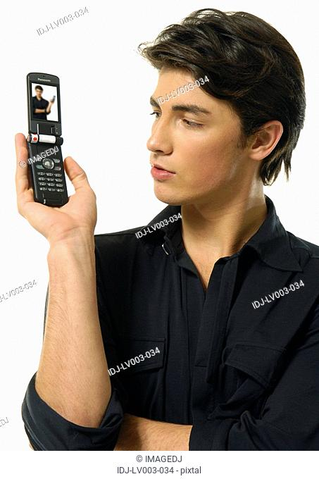 Close-up of a young man holding a mobile phone