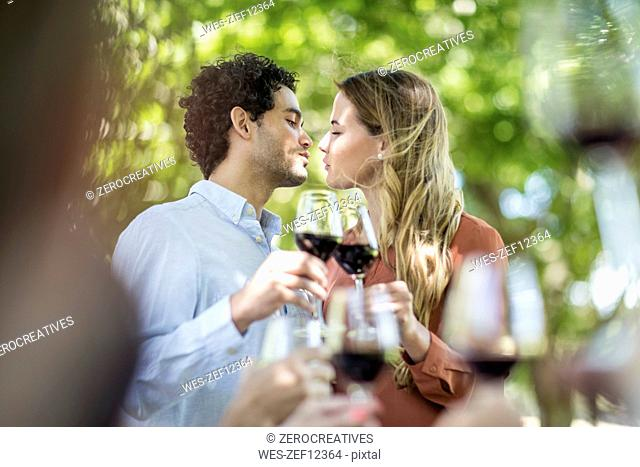 Couple kissing during lunch in garden with red wine