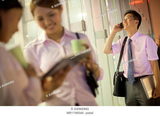 Young businessman talking on the phone, coworkers discussing on the foreground