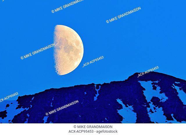 Half moon rising above mountain Stewart Cassiar Highway British Columbia Canada