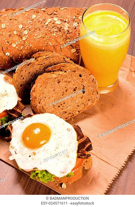 Fresh fried eggs and orange juice on the wooden table