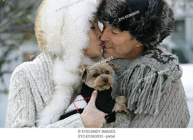 Mature couple kissing while holding a Yorkshire Terrier