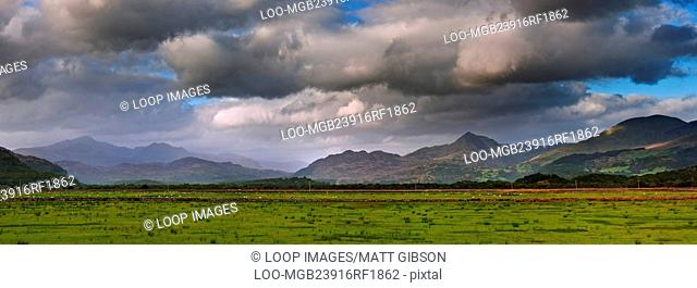 Stunning landscape image panorama view of Snowdon and mountain ranges in National Park in Wales at sunset