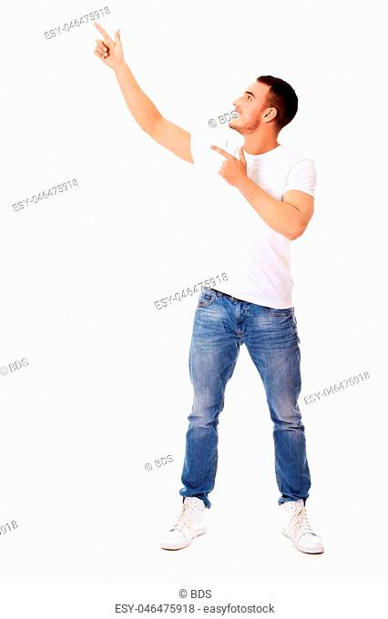 Happy young man pointing at copyspace or something