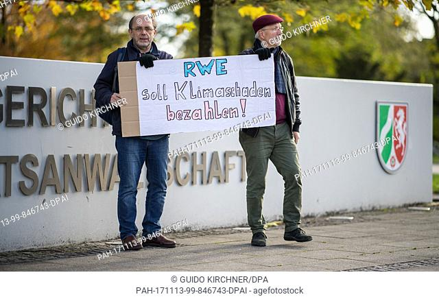 """Rolf Schwermer and Reinhard Suhling from Essen, of the organisation """"""""Fossil Free"""""""", holding a sign with which they demand that """"""""RWE should pay for climate..."""