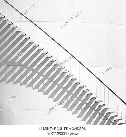 Steps leading up the side of a white storage tank at an oil refinery plant. A pattern of shadows