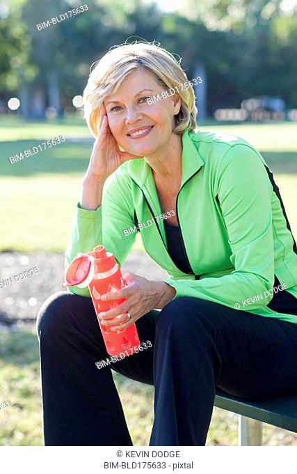 Caucasian woman drinking water bottle in park
