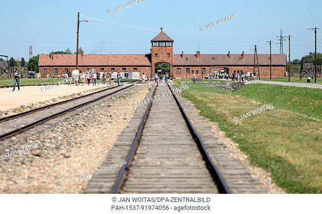Visitors walk in front of the historical gate through the former concentration camp Auschwitz-Birkenau in Oswiecim, Poland, 21 June 2017