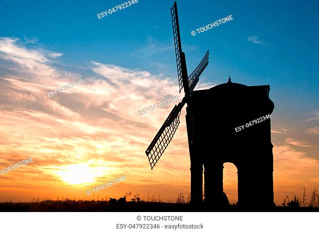 An old disused windmill silhouetted against a brilliant sunset and blue sky