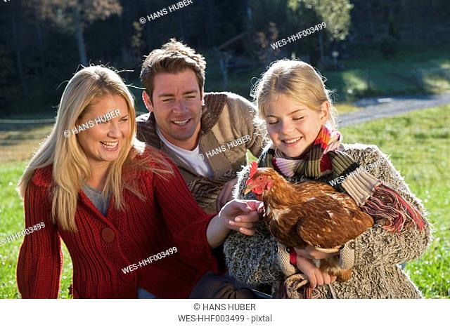 Austria, Salzburg, Flachau, Family standing on meadow with girl holding rooster