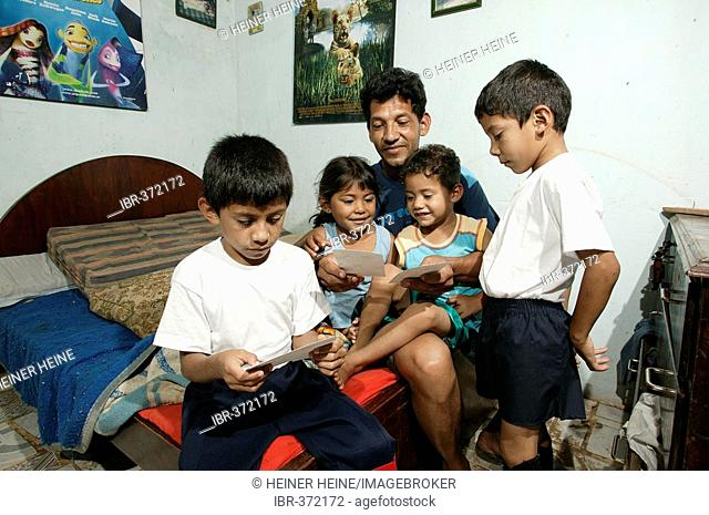 Guarani, father and children sitting on the bed and looking at pictures in the poor area of Chacarita, Asuncion, Paraguay, South America