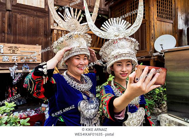 China, Guizhou, two Miao women wearing traditional dresses and headdresses taking a selfie with smartphone