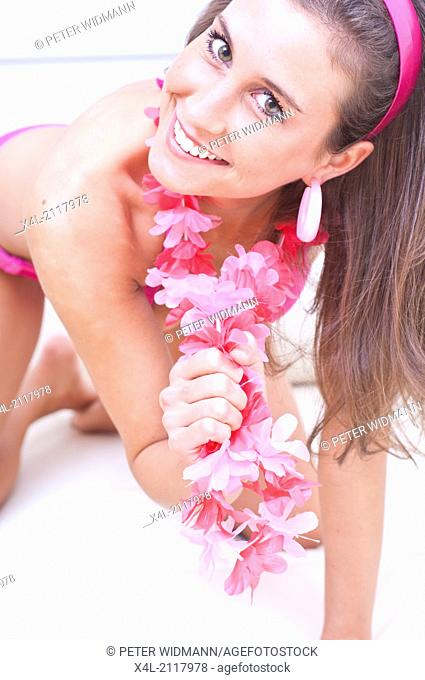 Young woman with pink flower necklace (model-released)
