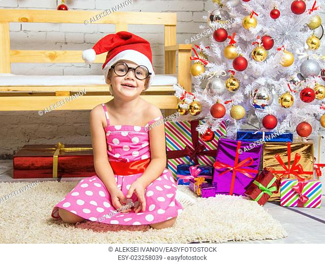 Girl in the red hat and the funny round glasses sits on a rug in the room with New Years interior