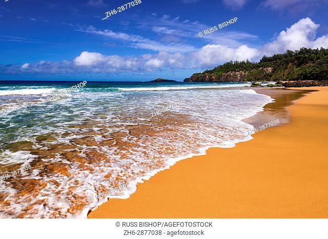 Surf and sand on Secret Beach (Kauapea Beach), Kilauea Lighthouse visible, Kauai, Hawaii USA