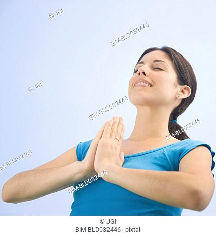 Low angle view of Hispanic woman praying