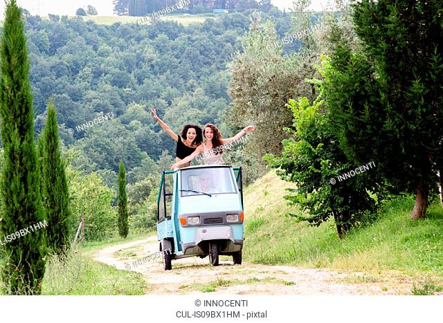 Friends on three-wheeler vehicle, Città della Pieve, Umbria, Italy