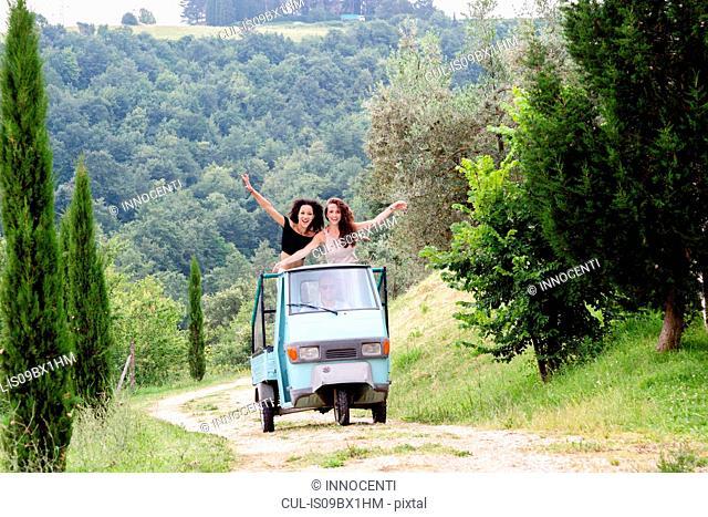 Friends on three-wheeler vehicle, Città della Pieve, Umbria, Italy