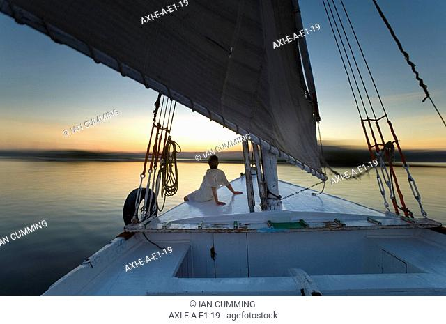 Woman relaxing on deck of felucca at dusk