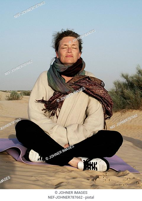Woman meditating in the desert, Tunisia