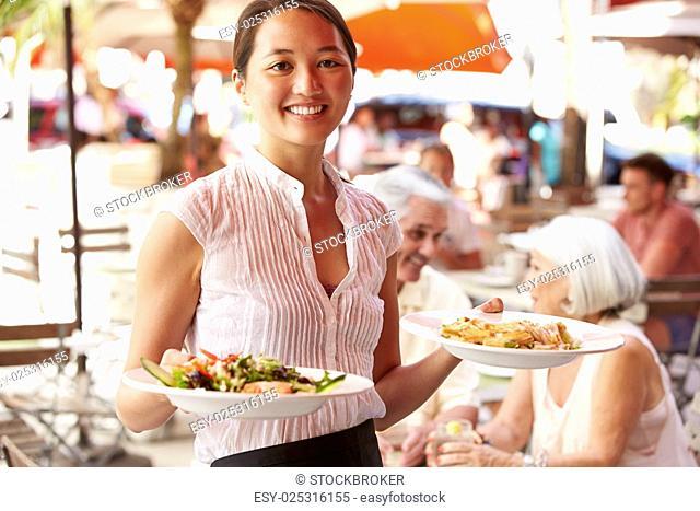 Waitress Serving Food At Outdoor Restaurant