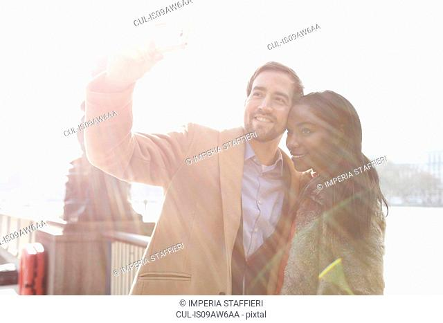 Couple standing beside river, taking self portrait using smartphone